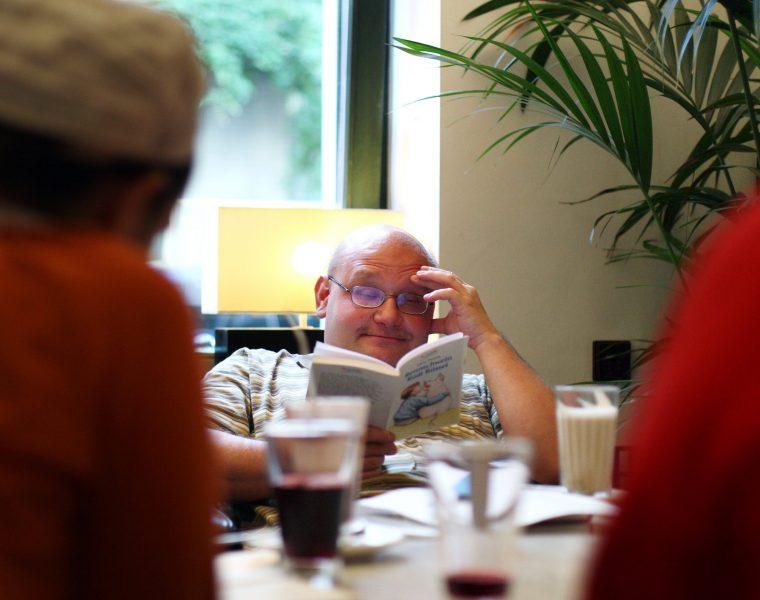 Mann mit Buch im Café