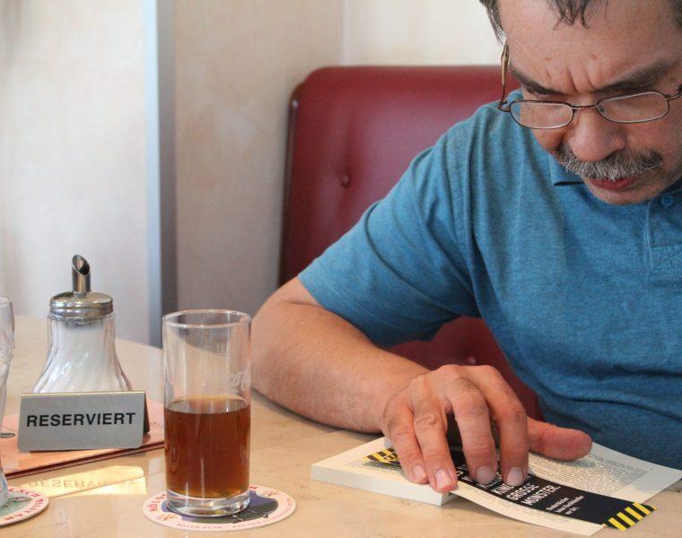 Mann liest ein Buch im Café