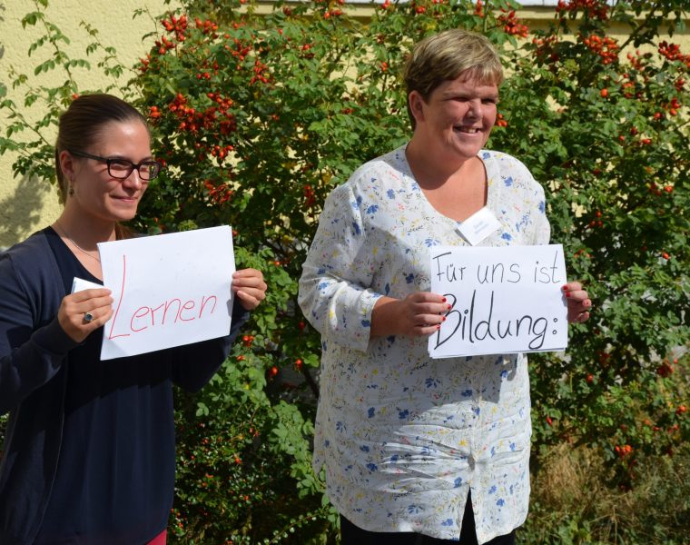 Zwei Frauen halten Plakate hoch, auf denen steht