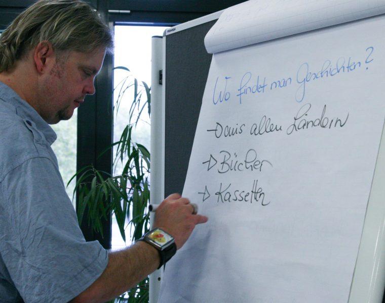 Mann schreibt an einem Plakat mit der Aufschrift