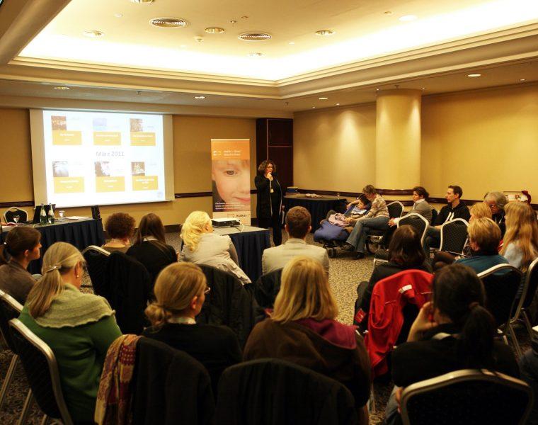 Workshop mit vielen Personen vor einer Rednerin